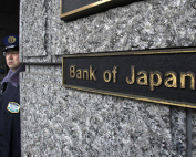 A security guard stands next to a signboard of the Bank of Japan at its headquarters in Tokyo