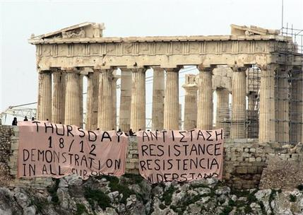 Backdropped by the ancient Parthenon, protesters can be seen after they placed giant banners off the Acropolis hill, in Athens, Wednesday Dec. 17, 2008. Protesters in Greece have hung the two banners over the ancient monument's walls with slogans calling for mass demonstrations and 'resistance' after days of violent protest sparked by the fatal police shooting of a teenager in Athens.(AP Photo/Lefteris Pitarakis)