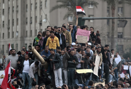 Egyptian anti-government protesters stand atop an Egyptian army tank during a protest in Tahrir square in Cairo, Egypt, Saturday, Jan. 29, 2011. (AP Photo/Lefteris Pitarakis)