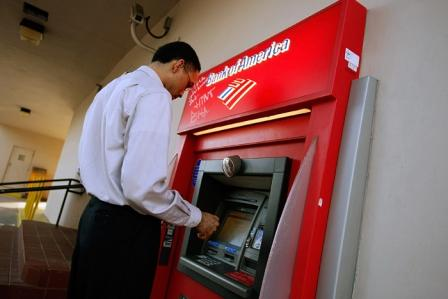 MIAMI - OCTOBER 18: A customer takes money out of a Bank of America ATM machine October 18, 2007 in Miami, Florida. Bank of America reported that their profits plummeted 32 percent in the third quarter of this year. (Photo by Joe Raedle/Getty Images)