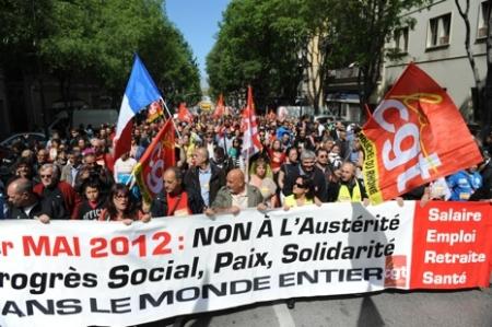 """Manifestants avec banderole, slogan """"1er Mai 2012: non a l'austerite, Progres social, Paix, Solidarite dans le monde entier """""""