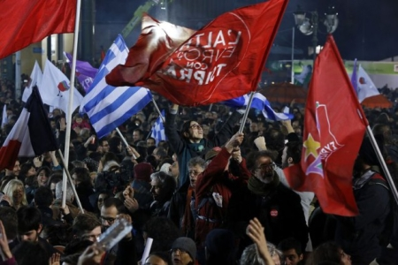 Supporters of radical leftist Syriza party chant slogans and wave Greek national and other flags after winning elections in Athens, January 25, 2015. Greek Prime Minister Antonis Samaras has called Tsipras to congratulate him on winning Sunday's snap election, a spokesman for Syriza and an official of the ruling conservative party said. REUTERS/Alkis Konstantinidis (GREECE - Tags: POLITICS ELECTIONS)