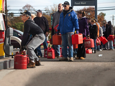 HAZLET TOWNSHIP, NJ - NOVEMBER 01: A man fills up jerry cans with gasoline as others wait in line on November 1, 2012 in Hazlet township, New Jersey. United States. Superstorm Sandy, which has left millions without power or water, continues to effect business and daily life throughout much of the eastern seaboard. Andrew Burton/Getty Images/AFP