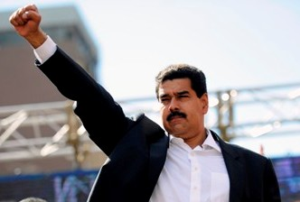 Venezuelan President Nicolas Maduro raises his fist during a rally in Caracas on November 12, 2013. Venezuela's ruling party eyed a vote Tuesday to pave the way for Maduro to govern by decree, broadening his powers, during an inflationary crisis a month before crucial municipal elections. AFP PHOTO/Leo RAMIREZ (Photo credit should read LEO RAMIREZ/AFP/Getty Images)